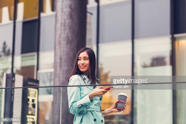 Japanese businesswoman walking and texting