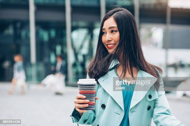 japanese businesswoman walking on the street - teal stock pictures, royalty-free photos & images