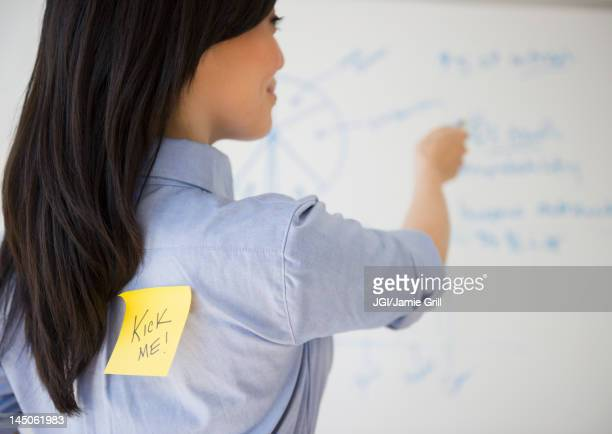 Japanese businesswoman with kick me note on back