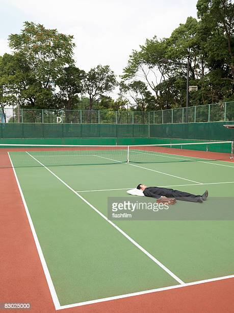 Japanese bussiness man sleeping on tennis court