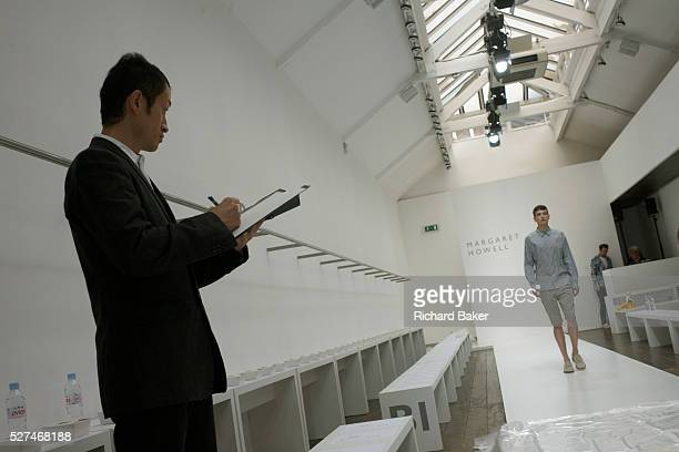 A Japanese buyer watches a male model walk the catwalk of couturier Margaret Howell's Fashion Week show rehearsal in the company's retail flagship...