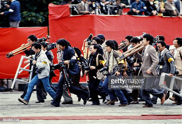 Japanese cameramen run to their positions to cover US President Ronald Reagan's arrival to greet Emperor Hirohito at the Akasaka Guest Palace...