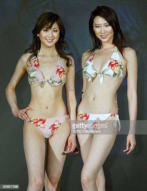 Japanese campaign girl Kana Watari and Chinese model Liuduo display bikinis printed with flower pattern during the swimwear show of Japan's...