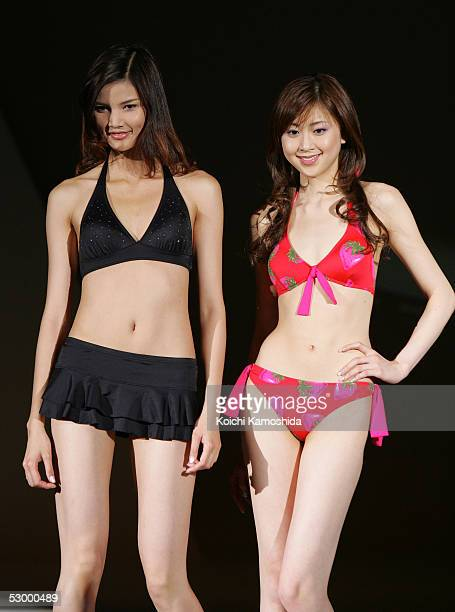Japanese campaign girl Kana Watari and Chinese model Mo Wandan walk the runway as they model new bikini fashions for 2005 during the Asahi Kasei...