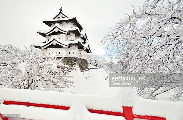 Japanese castle covered in snow Taken in Hirosaki northern Japan This castle is 400 years old The cherry blossom trees have a frozen layer of snow...