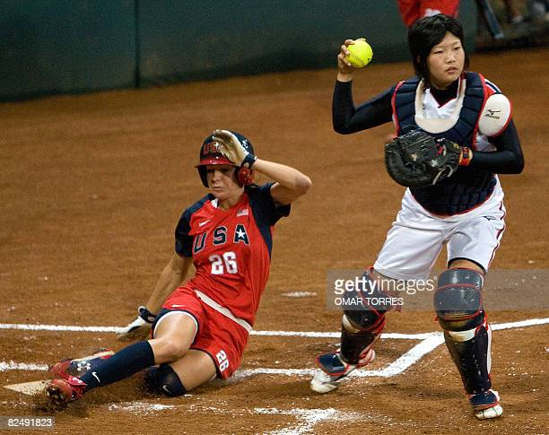 Japanese catcher Yukiyo Mine forces out at home plate US runner Caitlin Lowe in the bottom of the first inning during the 2008 Beijing Olympic Games...