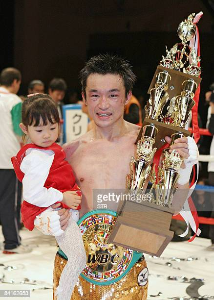 Japanese champion Toshiaki Nishioka holds his child and winning trophy after beating Mexican challenger Genaro Garcia at the World Boxing Council...