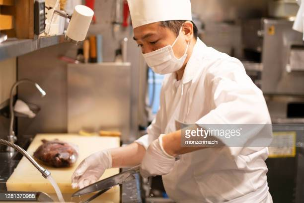 japanese chef cooking sea bream in the kitchen of japanese restaurant - catering building stock pictures, royalty-free photos & images
