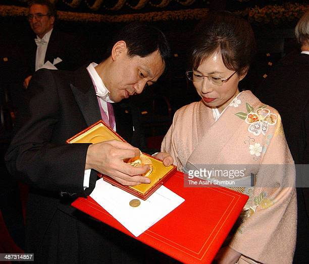 Japanese chemist Koichi Tanaka and his wife Yuko watch the Nobel Prize medal after the award ceremony at the Concert Hall on December 10 2002 in...