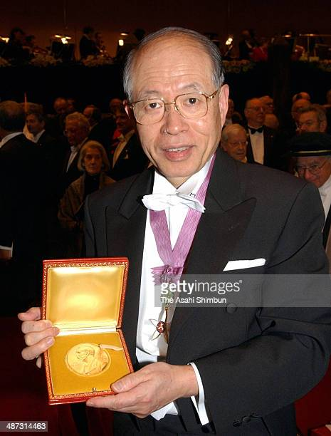 Japanese chemist Ryoji Noyori shows his Nobel Prize medal after the Nobel Prize Award Ceremony at the Concert Hall on December 10 2001 in Stockholm...