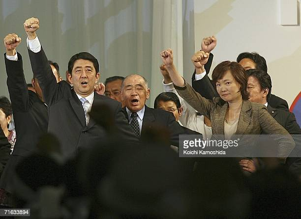 Japanese Chief Cabinet Secretary Shinzo Abe and his wife Akie Abe raise their hands during a press conference to announce his intention to stand as...
