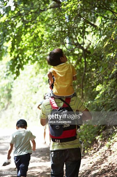 Japanische Kinder und Mann zu Fuß im Wald