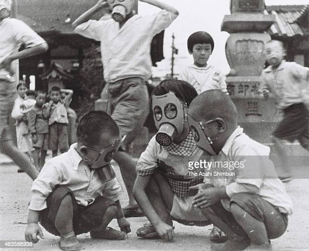 Japanese children play with wearing handmade gas masks circa 1940 in Japan