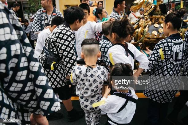 Japanese children wearing quothappiquot coats relax during break time just after carrying the portable shrine in Tokyo's one of the largest three day...