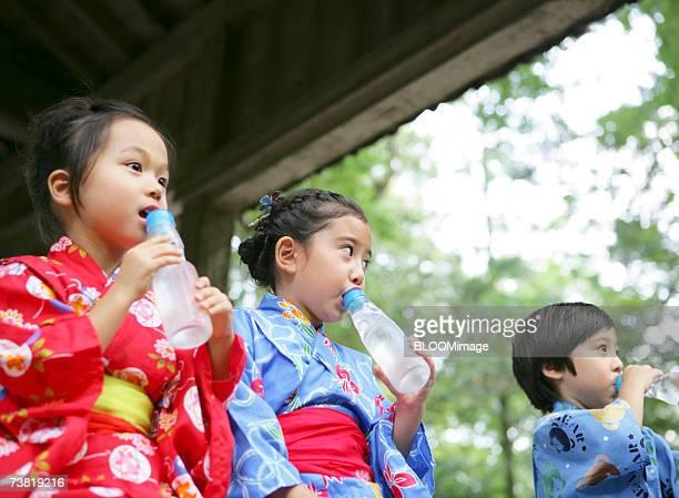 Japanese children wearing yukata drinking juice