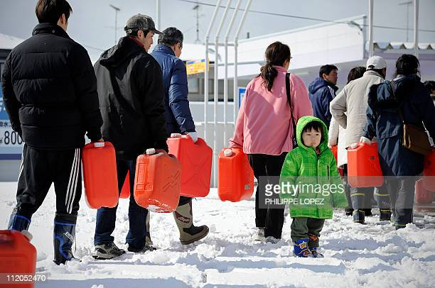Japanese citizens queue for petrol at a filling station in Ichinoseki in Iwate prefecture on March 17 2011 as basic supplies remain scarce in regions...
