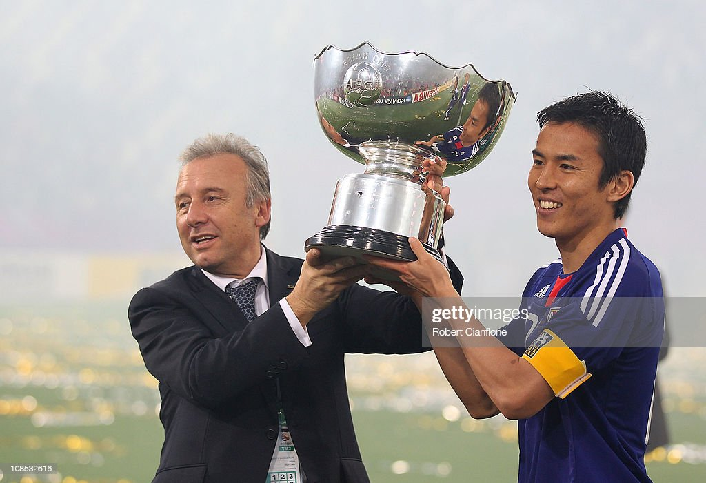Japanese coach Alberto Zaccheroni and captain Makato Hasebe hold the winners trophy after Japan defeated Australia in extra time 1-0 at the AFC Asian Cup Final match between the Australian Socceroos and Japan at Khalifa International Stadium on January 29, 2011 in Doha, Qatar.
