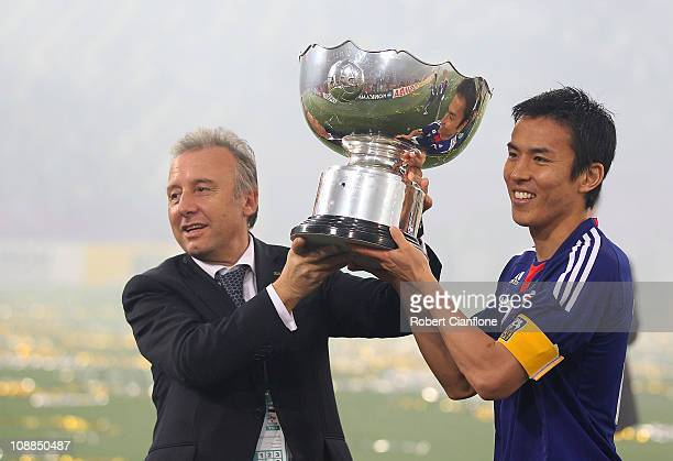 Japanese coach Alberto Zaccheroni and captain Makato Hasebe hold the winners trophy after Japan defeated Australia in extra time 10 at the AFC Asian...