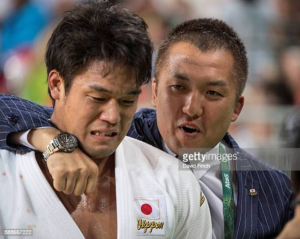 Japanese coach and 2004 Olympic gold medallist Keiji Suzuki consoles an emotional Ryunosuke Haga after he won the u100kg bronze medal during day 6 of...