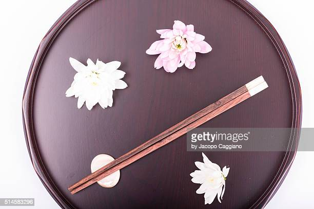 Japanese composition with chopsticks and flowers on a serving plate