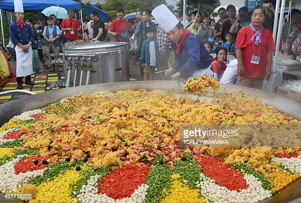 Japanese cooks in Tokyo make enough paella for 2000 people in a pan two metres in diameter on July 5 2014 Cooks at a Spanish restaurant used large...