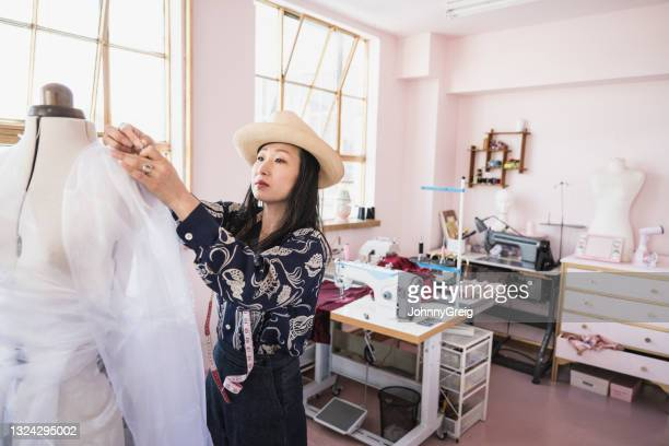 japanese costume designer pinning sheer fabric on dress form - sheer fabric stock pictures, royalty-free photos & images