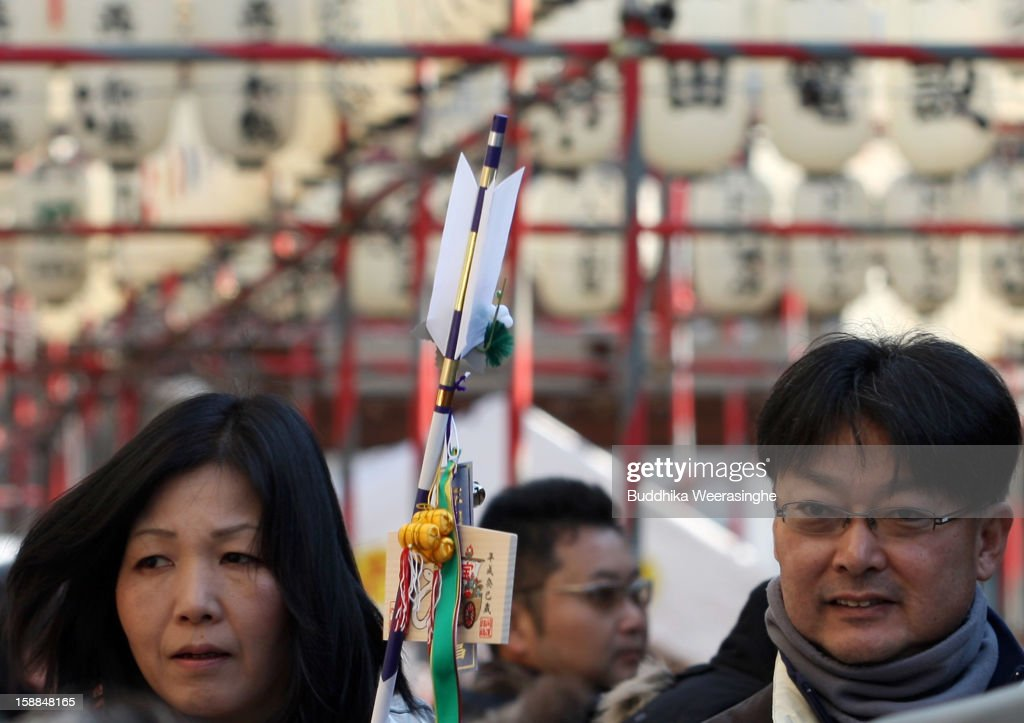 A Japanese couple carry 'Hamaya' (arrows intended to destroy evil spirits) to which 'Emas' (wooden plaques) are attached featuring a picture of a snake in celebration of the 'Year of the Snake' at Sosha Shrine on January 1, 2013 in Himeji, Japan. Japanese people visit the Buddhist temples and Shrine to pray for their health, happiness and prosperity during the New Year holidays.