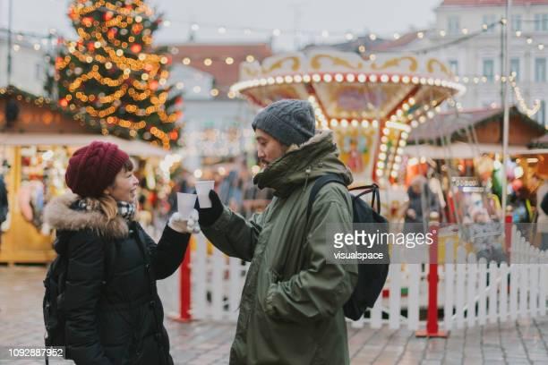 Japanese couple drinks mulled wine at Christmas market in Tallinn
