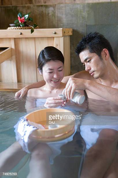 Japanese couple enjoying Sake in a hot tub, front view, Japan
