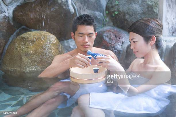 Japanese couple enjoying Sake in a hot tub, front view, side view, Japan
