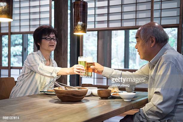 Japanese couple having dinner toasting with beer