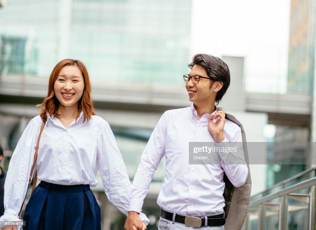 手をつないで、歩いて日本のカップルは、通りを下ってください。 : ストックフォト