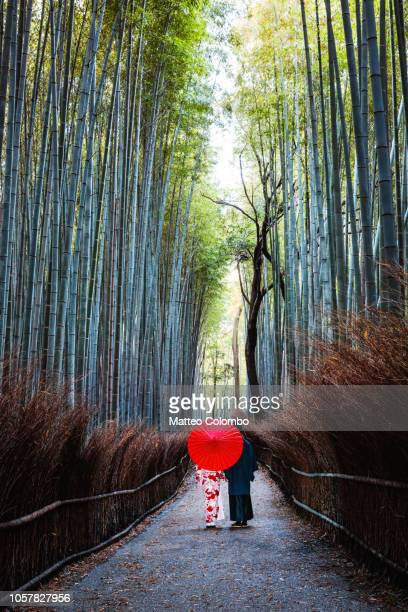 japanese couple in kimono walking in bamboo grove, kyoto, japan - kyoto japan stock photos and pictures