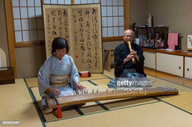 Japanese couple in traditional clothing in Kyoto Japan is playing the koto a traditional Japanese stringed musical instrument and the shakuhachi is a...