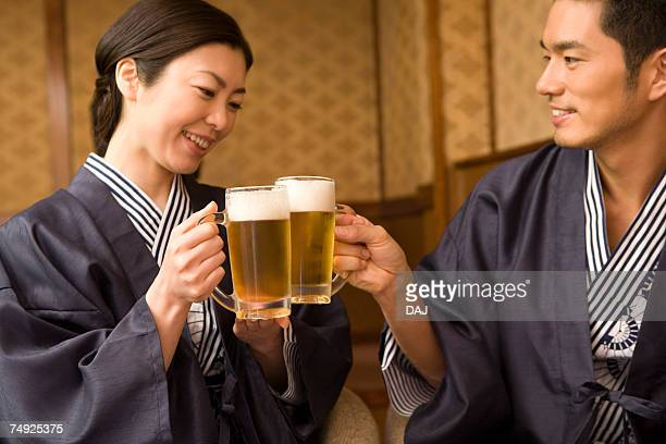 Japanese couple in Yukata toasting with beer, front view, side view, Japan