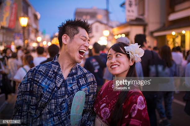 Japanese couple laughing with joy on street at festival