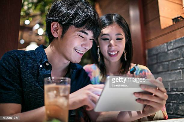 Japanese couple looking at a digital tablet in a cafeteria
