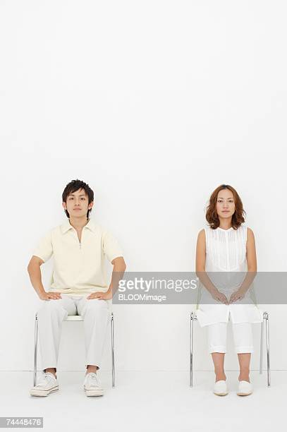 japanese couple looking at camera with sitting on chair - 椅子 ストックフォトと画像