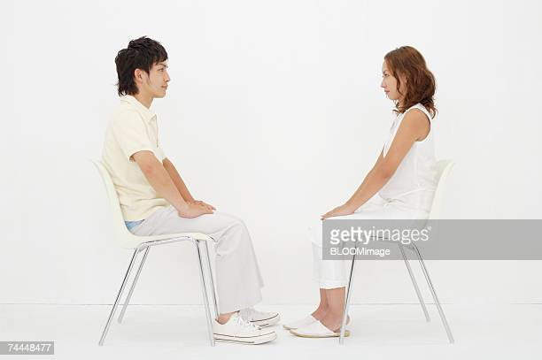 japanese couple looking at face each other with sitting on chair - 横からの視点 ストックフォトと画像