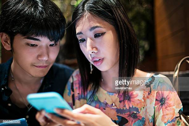 Japanese couple looking at the mobile phone at the cafeteria