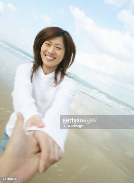 japanese couple playing with holding hand each other on beach - 人体部位 ストックフォトと画像