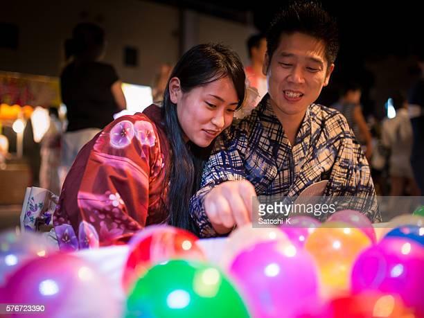 Japanese couple playing yo-yo fishing at festival