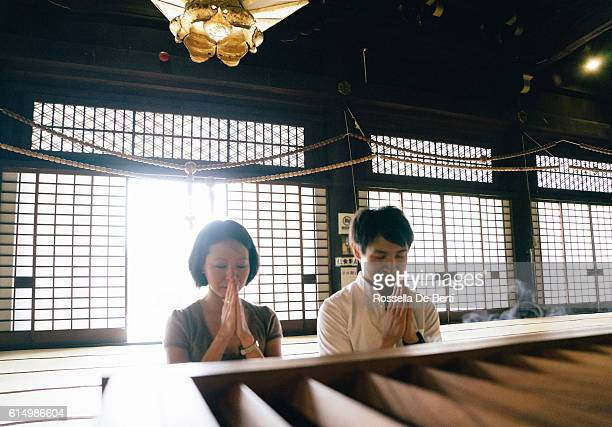 japanese couple praying in a buddhist temple - groothoek stockfoto's en -beelden