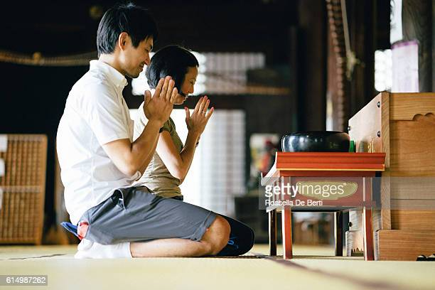 japanese couple praying in a buddhist temple - shrine stock pictures, royalty-free photos & images