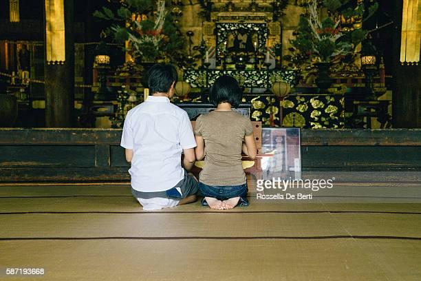 japanese couple praying in a buddhist temple, rear view - mulher orando de joelhos imagens e fotografias de stock