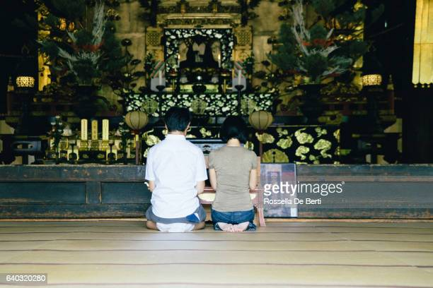 casal japonês rezar em templo budista, vista traseira - mulher orando de joelhos imagens e fotografias de stock