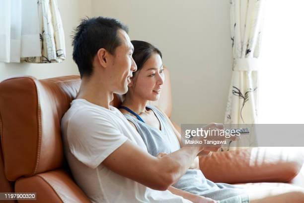 japanese couple sitting together on sofa - makiko tanigawa ストックフォトと画像