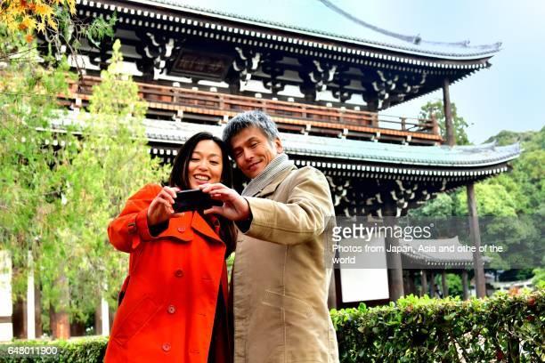 Japanese Couple Taking Selfie at Tofuku-ji Temple, Kyoto,