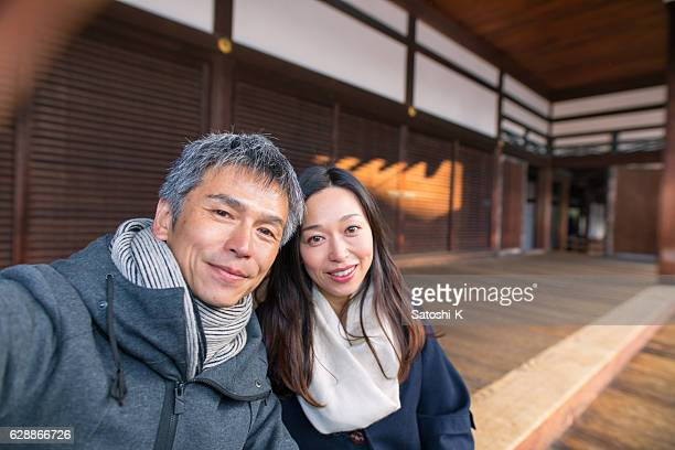 Japanese couple taking selfie picture in Tofukuji temple, Kyoto