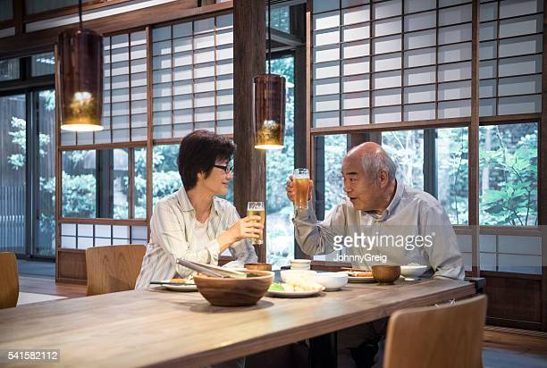 japanese couple toasting with beer glasses over dinner - asian drink stock photos and pictures